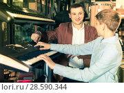 Купить «Father and teenage son examining keyboards in guitar shop», фото № 28590344, снято 29 марта 2017 г. (c) Яков Филимонов / Фотобанк Лори