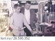 Купить «Boy and father choosing best drum», фото № 28590352, снято 29 марта 2017 г. (c) Яков Филимонов / Фотобанк Лори
