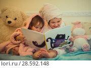 Купить «Little sisters in plush robe riding the book», фото № 28592148, снято 20 февраля 2017 г. (c) Julia Shepeleva / Фотобанк Лори
