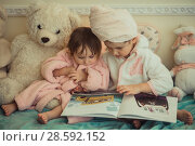 Купить «Little sisters in plush robe riding the book», фото № 28592152, снято 20 февраля 2017 г. (c) Julia Shepeleva / Фотобанк Лори