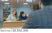 Купить «Serious students sitting for an examination writing notes», фото № 28592300, снято 21 февраля 2019 г. (c) Vasily Alexandrovich Gronskiy / Фотобанк Лори