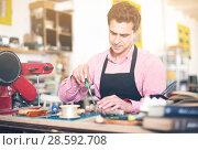Купить «Craftsman in uniform working in carpentry», фото № 28592708, снято 8 апреля 2017 г. (c) Яков Филимонов / Фотобанк Лори