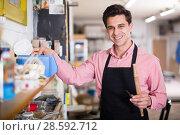 Купить «Carpenter standing in workshop», фото № 28592712, снято 8 апреля 2017 г. (c) Яков Филимонов / Фотобанк Лори