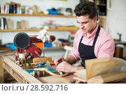 Купить «Craftsman in uniform working in carpentry», фото № 28592716, снято 8 апреля 2017 г. (c) Яков Филимонов / Фотобанк Лори