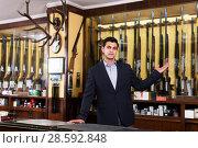 Купить «Salesman showing rifle», фото № 28592848, снято 11 декабря 2017 г. (c) Яков Филимонов / Фотобанк Лори