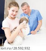 Купить «Smiling girl with puppy visiting veterinarian clinic», фото № 28592932, снято 3 мая 2018 г. (c) Яков Филимонов / Фотобанк Лори