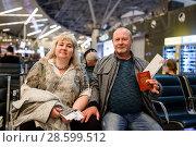 Купить «Город Москва. Немолодая пара держат в руках паспорт с авиабилетами в зале ожидания аэропорта Внуково», эксклюзивное фото № 28599512, снято 1 июня 2018 г. (c) Игорь Низов / Фотобанк Лори