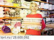Купить «Smiling senior seller is showing wide assortment of bed linen», фото № 28600092, снято 15 февраля 2017 г. (c) Яков Филимонов / Фотобанк Лори