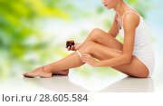 Купить «beautiful woman applying depilatory wax to her leg», фото № 28605584, снято 9 апреля 2017 г. (c) Syda Productions / Фотобанк Лори