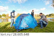 Купить «happy parents and son setting up tent at campsite», фото № 28605648, снято 27 сентября 2015 г. (c) Syda Productions / Фотобанк Лори