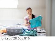 Купить «woman or housewife sorting laundry at home», фото № 28605816, снято 29 апреля 2018 г. (c) Syda Productions / Фотобанк Лори