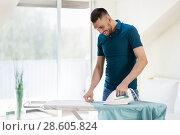 Купить «man ironing shirt by iron at home», фото № 28605824, снято 10 мая 2018 г. (c) Syda Productions / Фотобанк Лори