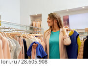 Купить «happy young woman choosing clothes in mall», фото № 28605908, снято 19 февраля 2016 г. (c) Syda Productions / Фотобанк Лори