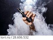 Купить «Girl soars on a black background vape», фото № 28606532, снято 9 июля 2016 г. (c) Светов Дмитрий Иванович / Фотобанк Лори
