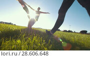 Купить «Legs of young woman walks forward to teenager team performs cheerleading tricks on the grass under the sun», видеоролик № 28606648, снято 21 июня 2018 г. (c) Константин Шишкин / Фотобанк Лори