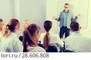 Купить «Young male lecturer answering near whiteboard in auditorium», фото № 28606808, снято 5 октября 2017 г. (c) Яков Филимонов / Фотобанк Лори