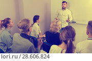 Купить «Young man lecturer answering near whiteboard», фото № 28606824, снято 5 октября 2017 г. (c) Яков Филимонов / Фотобанк Лори