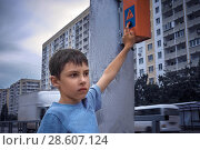 Купить «Little 7 years schoolboy pressing a button on traffic lights and waiting for green light», фото № 28607124, снято 17 ноября 2012 г. (c) Александр Сергеевич / Фотобанк Лори
