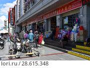 Тибет, Лхаса, Люди гуляют перед витринами магазинов (2018 год). Редакционное фото, фотограф Овчинникова Ирина / Фотобанк Лори