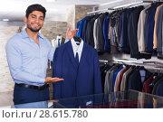 Купить «Man demonstrating suit in shop», фото № 28615780, снято 20 июня 2017 г. (c) Яков Филимонов / Фотобанк Лори
