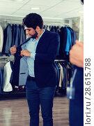 Купить «Male 25-33 years old is trying on jacket in front of the mirror», фото № 28615788, снято 20 июня 2017 г. (c) Яков Филимонов / Фотобанк Лори
