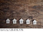 Купить «Несколько картонных домиков на деревянном фоне», фото № 28616176, снято 21 июня 2018 г. (c) Наталья Осипова / Фотобанк Лори