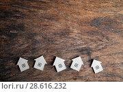 Купить «Несколько картонных домиков на деревянном фоне», фото № 28616232, снято 21 июня 2018 г. (c) Наталья Осипова / Фотобанк Лори