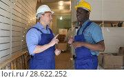 Купить «Confident builders discussing while examining room and planning construction works», видеоролик № 28622252, снято 21 мая 2018 г. (c) Яков Филимонов / Фотобанк Лори