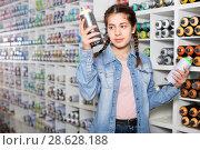 Купить «Portrait of girl choosing paint color in aerosol can in art shop», фото № 28628188, снято 12 апреля 2017 г. (c) Яков Филимонов / Фотобанк Лори