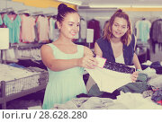 Купить «Female friends choosing trousers in shop», фото № 28628280, снято 19 июня 2017 г. (c) Яков Филимонов / Фотобанк Лори