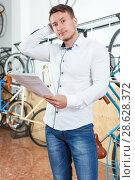 Купить «Man is selecting bicycle with bike characteristic», фото № 28628372, снято 14 мая 2018 г. (c) Яков Филимонов / Фотобанк Лори