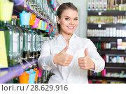 Купить «Cheerful attractive girl standing in interior of perfume shop, showing thumbs up», фото № 28629916, снято 24 апреля 2018 г. (c) Яков Филимонов / Фотобанк Лори