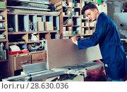 Positive guy fixing chipboard on table at workshop. Стоковое фото, фотограф Яков Филимонов / Фотобанк Лори