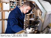 Купить «Young male joiner working with trimming machine», фото № 28630108, снято 7 ноября 2016 г. (c) Яков Филимонов / Фотобанк Лори