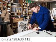 Купить «Man processing plank at workshop», фото № 28630112, снято 7 ноября 2016 г. (c) Яков Филимонов / Фотобанк Лори