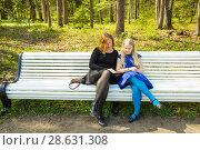 Купить «Blonde girl and her mother sitting on a settle in a park and reading interesting book», фото № 28631308, снято 21 мая 2017 г. (c) Сергей Дубров / Фотобанк Лори