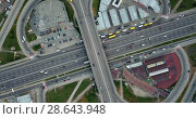 Купить «Aerial video from the drone in 4K. Road junction in the area of the metro Poznyaki highway and overpass with cars and trucks, in Kiev, Ukraine. Dolly-out motion and drone movement counter-clockwise.», видеоролик № 28643948, снято 8 мая 2018 г. (c) Ярослав Данильченко / Фотобанк Лори