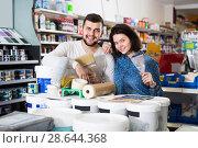 Купить «Young couple demonstrating tools for house renovating in paint store», фото № 28644368, снято 9 марта 2017 г. (c) Яков Филимонов / Фотобанк Лори