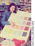 Купить «friendly female customer examining color scheme variants in paint store», фото № 28644384, снято 9 марта 2017 г. (c) Яков Филимонов / Фотобанк Лори