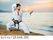 Купить «Man in uniform doing taekwondo exercises at sunset sea shore», фото № 28644396, снято 19 июля 2017 г. (c) Яков Филимонов / Фотобанк Лори
