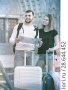 Купить «Couple of smiling tourists with map and baggage», фото № 28644452, снято 25 мая 2017 г. (c) Яков Филимонов / Фотобанк Лори