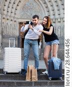 Купить «female and male standing with baggage at street and taking selfie», фото № 28644456, снято 25 мая 2017 г. (c) Яков Филимонов / Фотобанк Лори