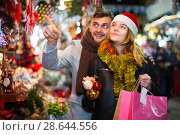 Купить «Young couple in hat at Christmas fair, man points to toys», фото № 28644556, снято 14 декабря 2017 г. (c) Яков Филимонов / Фотобанк Лори