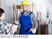 Купить «Professional constructor with spatula is talking to client», фото № 28644628, снято 3 июня 2017 г. (c) Яков Филимонов / Фотобанк Лори