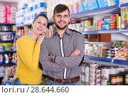 Купить «Glad couple standing among shelves», фото № 28644660, снято 20 января 2018 г. (c) Яков Филимонов / Фотобанк Лори