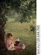Купить «Маленькая девочка читает книгу в саду», фото № 28644760, снято 18 июня 2018 г. (c) Julia Shepeleva / Фотобанк Лори