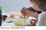 Купить «Mother hand with her child mixing the dough for preparing pancakes», фото № 28645072, снято 19 июля 2018 г. (c) Константин Шишкин / Фотобанк Лори