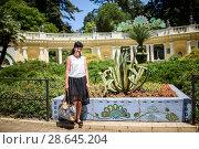 """Купить «Город Сочи, Парк """"Дендрарий"""" . Симпатичная женщина стоит на фоне входа в парк», эксклюзивное фото № 28645204, снято 1 июня 2018 г. (c) Игорь Низов / Фотобанк Лори"""