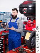 Купить «Smiling male worker counting sum for his service», фото № 28646064, снято 14 августа 2018 г. (c) Яков Филимонов / Фотобанк Лори