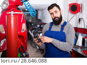 Купить «Person is calculating sum for repairing motorcycle», фото № 28646088, снято 21 сентября 2018 г. (c) Яков Филимонов / Фотобанк Лори